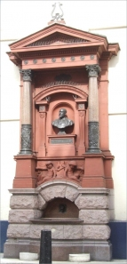 The Sir Augustus Harris Memorial Drinking Fountain outside the Theatre Royal, Drury Lane.  The fountain was erected by public subscription and unveiled on 1 November 1897 by the Lord Mayor.  The bust was by T. Brock, RA and the overall design by Sidney R. J. Smith.